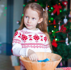 Little girl baking gingerbread cookies for Christmas at kitchen