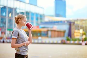 Girl drinking coffee at La Defense in Paris