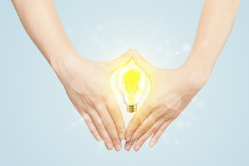 Hands creating a form with light bulb