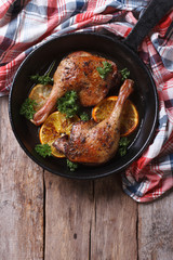 Fried duck leg with oranges in a pan vertical top view