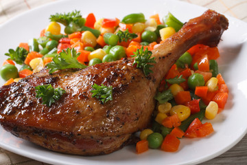 delicious roasted duck leg with vegetables on white plate