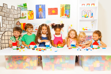 Little boys and girls constructing toy houses