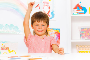 Boy showing letter flashcard in reading class