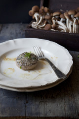 one stuffed mushroom on plate on table with raw mushrooms