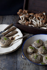 stuffed mushrooms on wooden table with plate and raw mushrooms