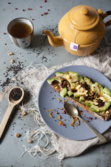 wholemeal vegan toast with avocado slices and seeds with teapot