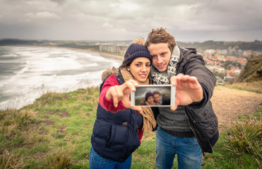 Young couple taking selfie photo with smartphone outdoors in a