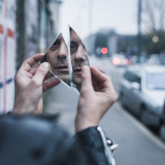 Punk guy looking at himself in a shattered mirror