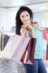 Happy indian woman carrying shopping bags