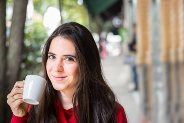 Portrait of happy beautiful brunette with mug in hand