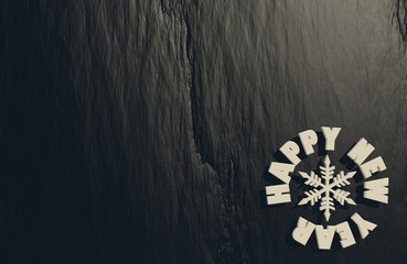 happy new year text and snowflake icon on black stone relief