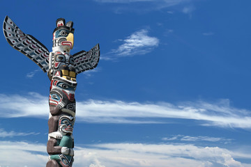Totem wood pole in the blue cloudy background
