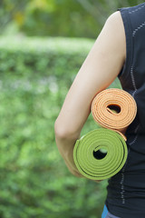 Young woman holding a yoga mats