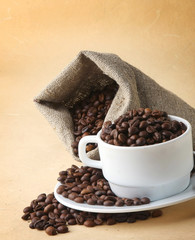 A sack of coffee beans and a cup, isolated on brown