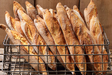 French baguettes in metal basket in bakery