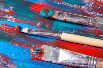 brushes and acrylic paint background with blue and red strokes