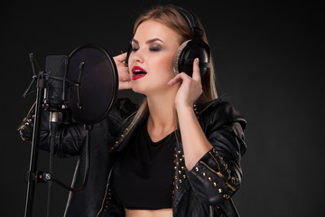 Portrait of a beautiful woman singing into microphone with