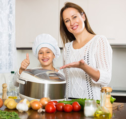 mother and  daughter using multicooker