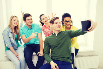 smiling students making picture with tablet pc