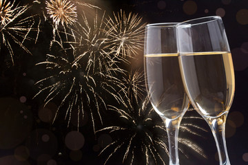 Glasses with champagne against fireworks