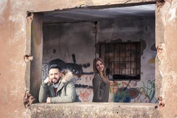Chicos guapos posando en una ventana de una casa antigua