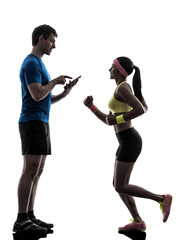 Wall Mural - woman exercising jogging man coach using digital tablet  silhoue