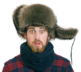 Young bearded man in the earflaps hat looks silly