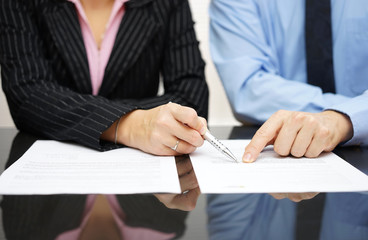 businessman and businesswoman are pointing to .article of the tr