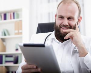 lachender Arzt schaut etwas auf seinem Tablet Computer