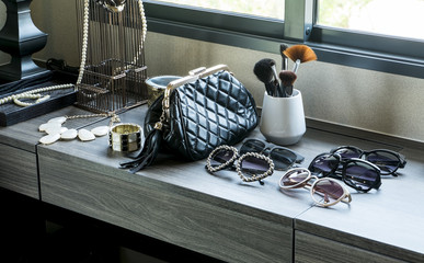 handbag,sunglasses, jewelry and makeup brushes on a black table
