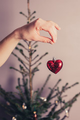 Hand holding heart by christmas tree