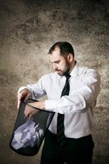 Man searching document in paper bin