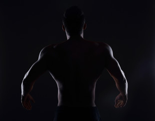Rear view of healthy muscular young man , silhouette