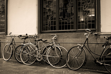 Bicycles leaning against old wall in sepia