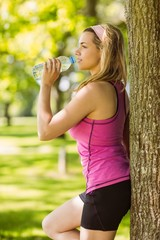 Fit blonde leaning against tree drinking water