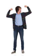 Shouting young man flexing muscles