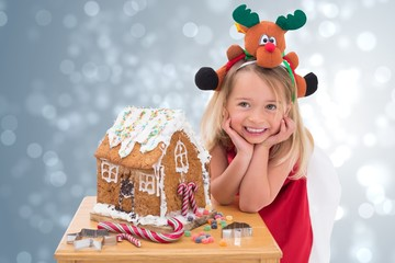 Composite image of festive little girl making gingerbread house