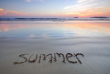 Summer words written in a beach at sunset