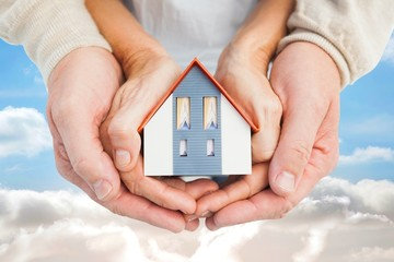 Composite image of couple holding small model house in hands