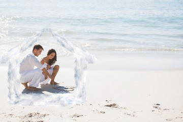 Composite image of cute couple drawing a heart in the sand