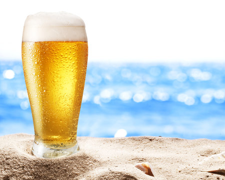 Photo of cold beer botle in the sand.