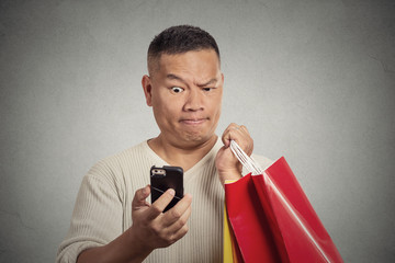 surprised man holding shopping bags looking at smartphone