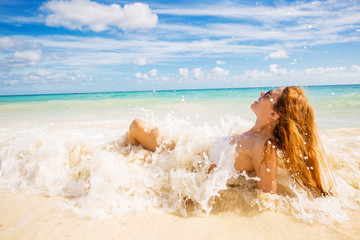 woman with sunglasses laying on beach covered in ocean waves