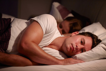Man awake while woman is sleeping, caused by insomnia.