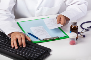 Doctor's hand typing on keyboard