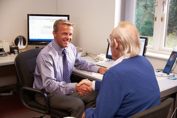 Doctor Greeting Senior Male Patient With Handshake