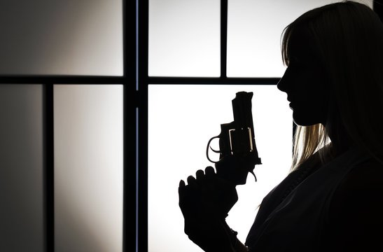 Silhouette of fashion killer woman with revolver pistol