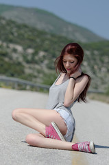 Very attractive model standing in the middle of a mountain road