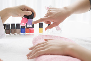woman who chooses the color of the nail polish