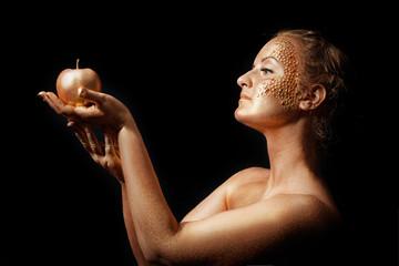 girl with golden bodyart posing with golden apple in her hand